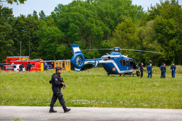 Polícia a hasiči stoja neďaleko vrtuľníkov v La Chapelle-sur-Erdre.