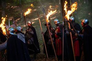 Zbrojnoši, ktorí obkľúčili vlčicu pred jaskyňou.