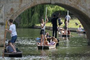 Ľudia sa plavia na člne na rieke Cam v anglickom meste Cambridge.