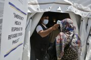 Uchádzačke o azyl, ktorá čaká na dávku vakcíny proti ochoreniu COVID-19 od spoločnosti Johnson & Johnson, merajú telesnú teplotu pred vstupom do očkovacieho stanu v utečeneckom tábore na gréckom ostrove Lesbos.