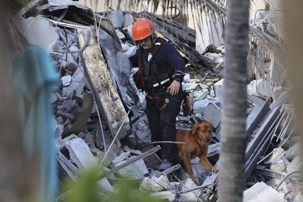 Hasič so psom prehľadávajú trosky časti dvanásťpodlažného obytného domu, ktorá sa zrútila v kalifornskom meste Surfside.