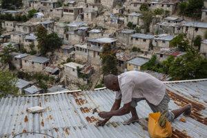Muž zabezpečuje strechu domu pred tropickou búrkou Elsa v Port-au-Prince na Haiti.