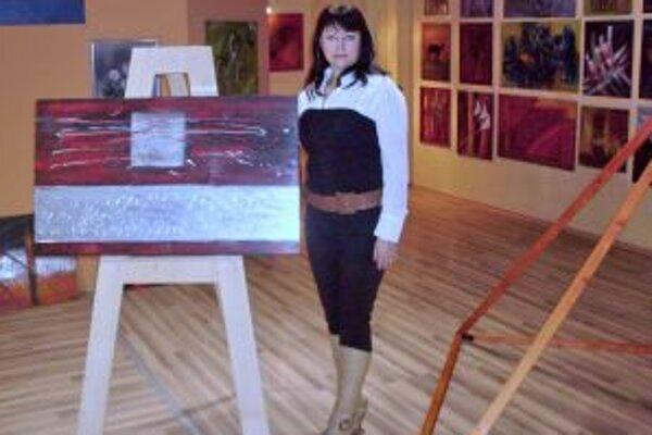 Mária Šefferová so svojimi dielami, vpravo relaxačná pyramída.