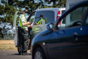 Policajt vykonáva hraničnú kontrolu pri vstupe na Slovensko.