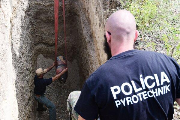 Policajný pyrotechnik dohliada na vykladanie leteckej bomby.