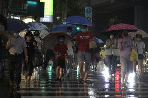 Ľudia v uliciach Šanghaja pred príchodom tajfúnu In-Fa