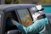 Odber vzoriek na odbernom mieste, ktoré slúži na testovanie nového koronavírusu u ľudí priamo z okna auta v Záhrebe.