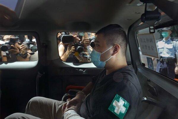 Na archívnej snímke zo 6. júla 2020 Tchang Sing-ťie sedí v policajnej dodávke počas príchodu do budovy súdu v Hongkongu.