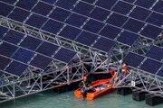 Pracovníci zostavujú plávajúce člny so solárnymi panelmi v priehradnej nádrži Lac des Toules vo švajčiarskom Bourg-Saint-Pierre 8. októbra 2019.