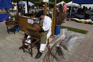 Košikár pletie prútený košík počas pokračovania 61. ročníka Medzinárodného folklórneho festivalu v Myjave.