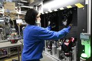 Zamestnankyňa pracuje na spájaní komponentov zadného svetla vo výrobnej hale spoločnosti Hella.