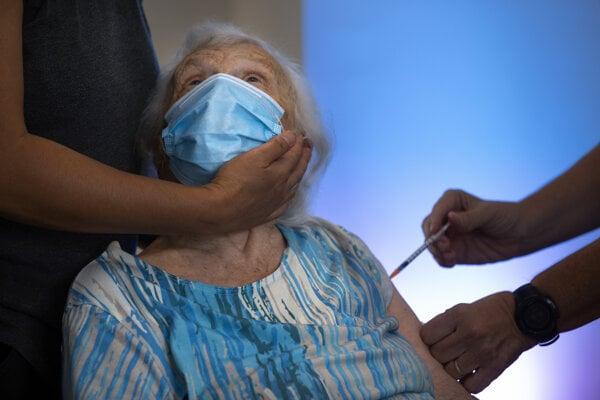 Osemdesiatšesťročná Blossom Koppelmanová dostáva tretiu dávku vakcíny proti ochoreniu COVID-19 v domove dôchodcov v izraelskom meste Netanja.