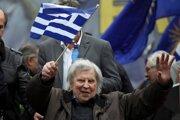 Na archívnej snímke z februára 2018 máva Mikis Theodorakis gréckou zástavou počas manifestácie v Aténach.