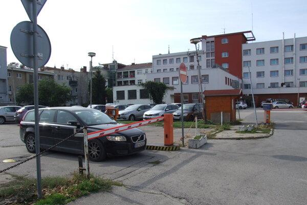 Na vjazde na hotelové parkovisko je rampa. Vzadu vidieť hotel, vľavo je bytovka.