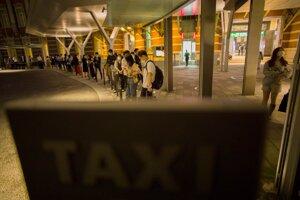 Ľudia čakajú v dlhom rade na taxíky pred stanicou po silnom zemetrasení.