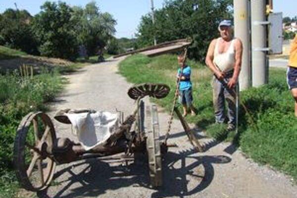 Majiteľ koní pri zdemolovanej kosačke. Kone ju za sebou ťahali asi kilometer. V dedine ňou zasiahli auto.