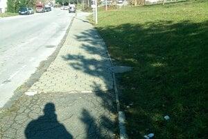 Odpadky popri chodníku medzi SOŠ a Billou v Sásovej