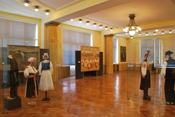 Paintings mix with authentic folk costumes in museum's big hall.