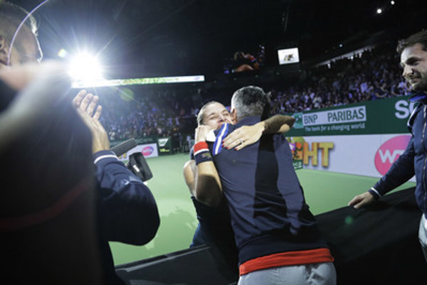 Dominika Cibulková hugs her fitness coach and physio, Jozef Ivanka, with her coach Matej Lipták right and her husband, Michal Navara, left, after her victory at the WTA championship in Singapore, October 30