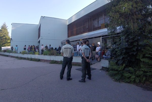 Police officers are watching people in the queue in front of Bratislava's Foreigners' Police department.