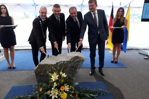 Kežmarok Mayor Ján Ferenčák, PM Peter Pellegrini, Mubea owner Thomas Muhr and Economy Minister Peter Žiga, from left, tapping the foundation stone of the brand new Mubea plant in Kežmarok Industrial Park.