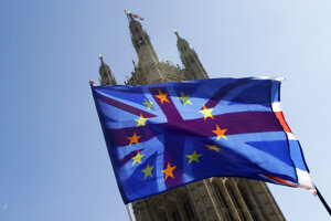 A British Union flag is flown behind a European Union flag, backdropped by Parliament in London on April 10, 2019.