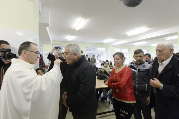 Priest Peter Brenkus (L) of Serenity and Good gives holy Communion to Assyrian Christians at the end of mass celebrated together with Father Douglas Bazi upon Assyrians'arrival.