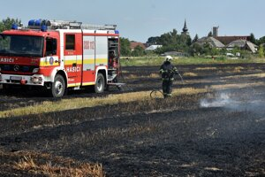 A fire fighter puts out a fire in the field in the town of Vojčice, eastern Slovakia, on July 16, 2019.
