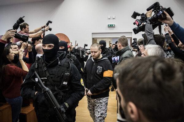 Miroslav Marček is escorted to the courtroom.