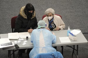 Healthcare worker registers a senior in vaccination centre, Trenčín.