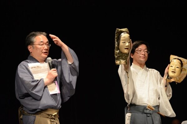 Head of Yamamoto Noh theatre and his apprentice explain masks in a workshop.