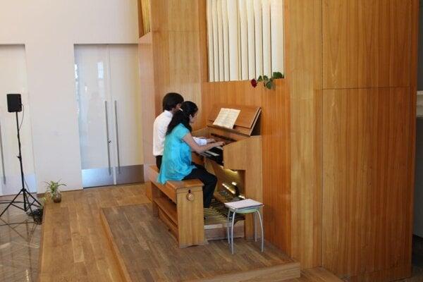 Gai and Yoshida playing one organ.