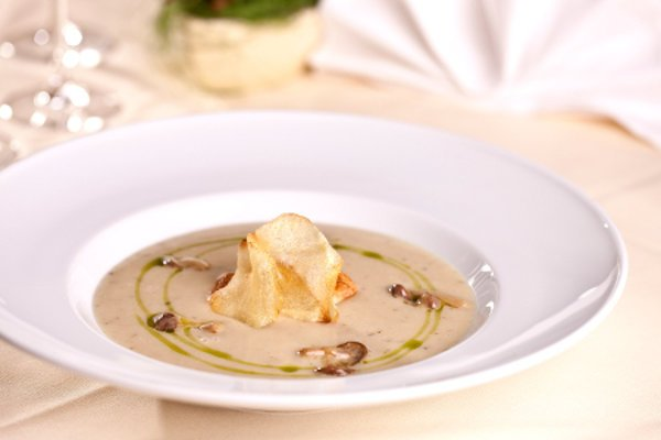 Potato mushroom cream soup served with chive oil and potato chips