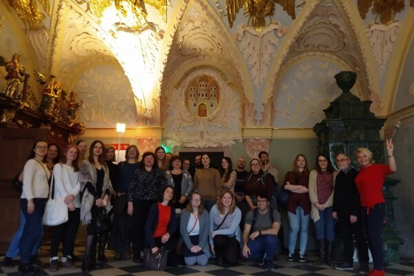 Foreigners and Slovaks in Bratislava pose in the beautiful interior of the Old Town Hall.