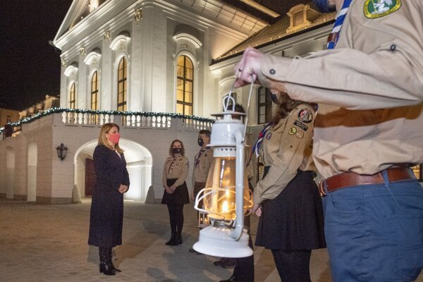 Slovak President Zuzana Čaputová accepts the Peace Light of Bethlehem from scouts at the Presidential Palace on December 15, 2020. The tradition, launched in Austria in 1987, has spread to many European countries and the Americas since then.