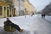 A man wearing a face covering sits in an armchair on the snow-covered Main Street in Košice on January 13, 2021.