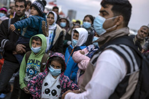 Refugees and migrants waiting for a bus at the port of Piraeus near Athens on May 4, 2020.