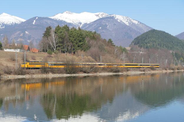 Popri vodnej priehrade Krpeľany jazdí 9. marca 2021 vlak na severe Slovenska obklopený národnými parkmi Malá Fatra a Veľká Fatra.