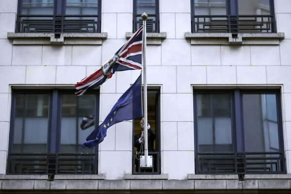 A member of protocol removes the EU flag from the UK Permanent Representation to the EU in Brussels on January 31, 2020.
