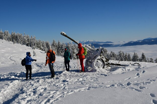 Hikers stand next to a cannon in Sedlo Okopy during a winter hike to the top of Minčol.