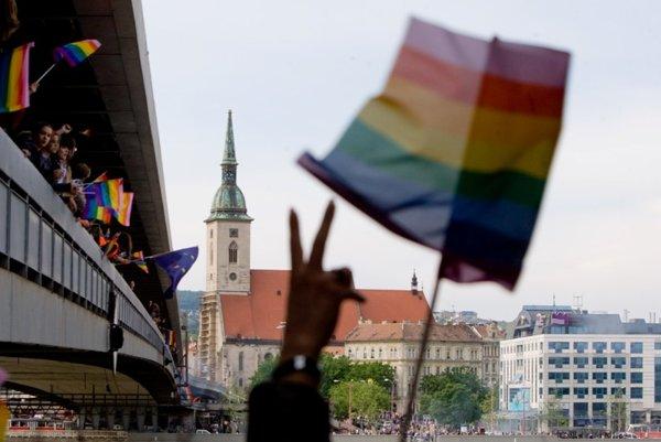 Pride participants crossing Bratislava's New Bridge waving their rainbow flags.