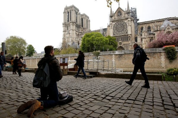 Man kneels as people came to watch and photograph the Notre Dame cathedral after the fire in Paris, April 16, 2019.