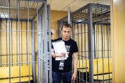 Ivan Golunov, a prominent Russian investigative reporter, who worked for the independent website Meduza, leaves the cage in a court room in Moscow, Russia on June 8, 2019.