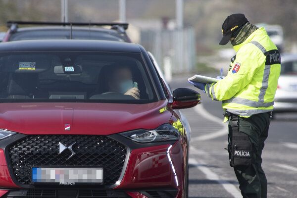 A police officer checks a vehicle in Bratislava during the coronavirus outbreak on April 6, 2020.
