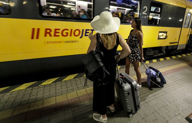 Holidaymakers in Bratislava get on a train from Prague, heading for Croatia, on June 30.