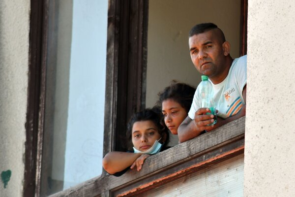 Two Roma sisters and their father look out the window in the town of Vranov nad Topľou, eastern Slovakia, on August 22, 2020.