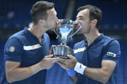 Slovakia's Filip Polasek (left) and Croatia's Ivan Dodig kiss their trophy after defeating Rajeev Ram of the US and Britain's Joe Salisbury in the men's doubles final at the Australian Open tennis championship in Melbourne, Australia, Sunday, Feb. 21, 2021.