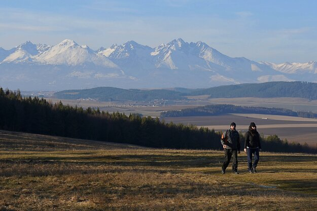 Tourists walk through a meadow near the Tomášovský výhľad viewpoint in the Slovenský raj national park. A panorama of the High Tatras can be seen in the background.