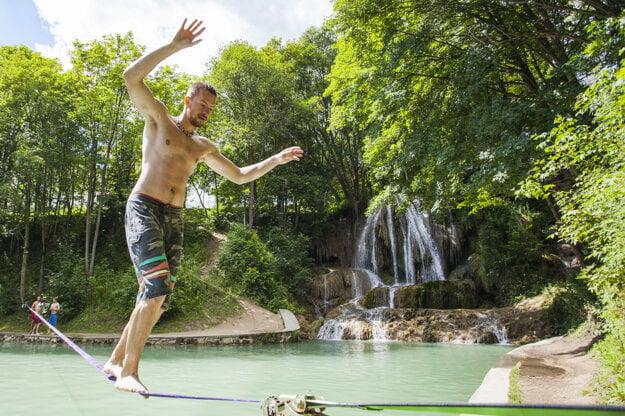 A man walks a tightrope over the Lúčky Waterfall.