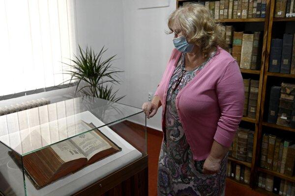 The Košice library head Darina Kožuchová stands by the Károlyi Bible.